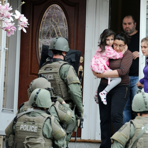 Police search the home of an unidentified family on Nichols Ave in Watertown during a massive manhunt for the Boston Marathon bombing suspect on Friday afternoon, April 19, 2013.